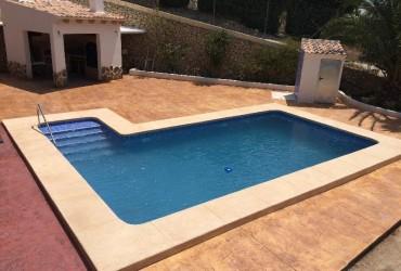 Piscina rectangular de 8×4, barbacoa y terraza de hormigon impreso.